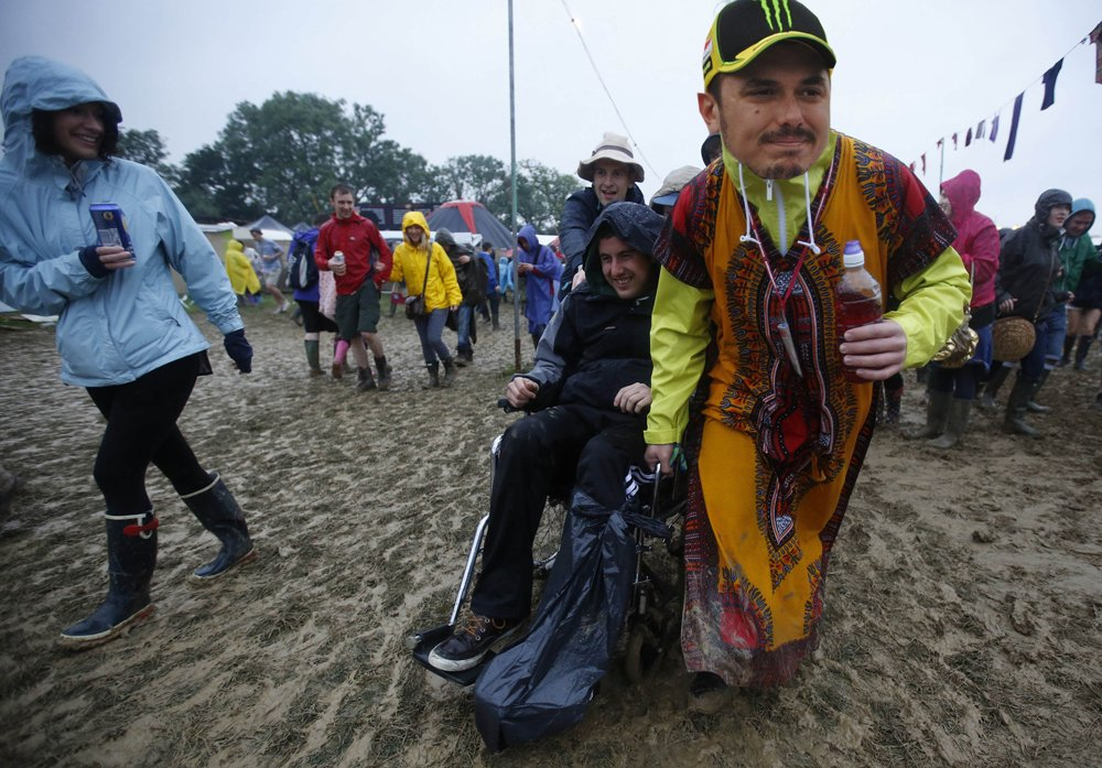 Festival goers push a man in a wheelchair through the mud on the second day of Glastonbury music festival at Worthy Farm in Somerset